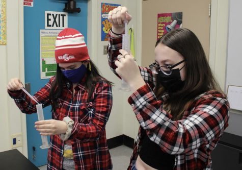 Juniors Elizabeth Rose and Samantha Willet distribute water from a beaker for a  lab experiment in their AP Environmental Science class. With each class period  lasting 91 minutes, students have more time to do different assignments, such as  conducting more labs throughout the school year.